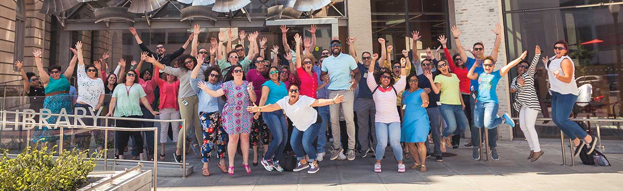 Commercial Web Services Employees Jumping In Front of Slover Library